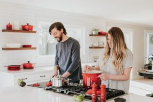 man and woman cooking in home kitchen